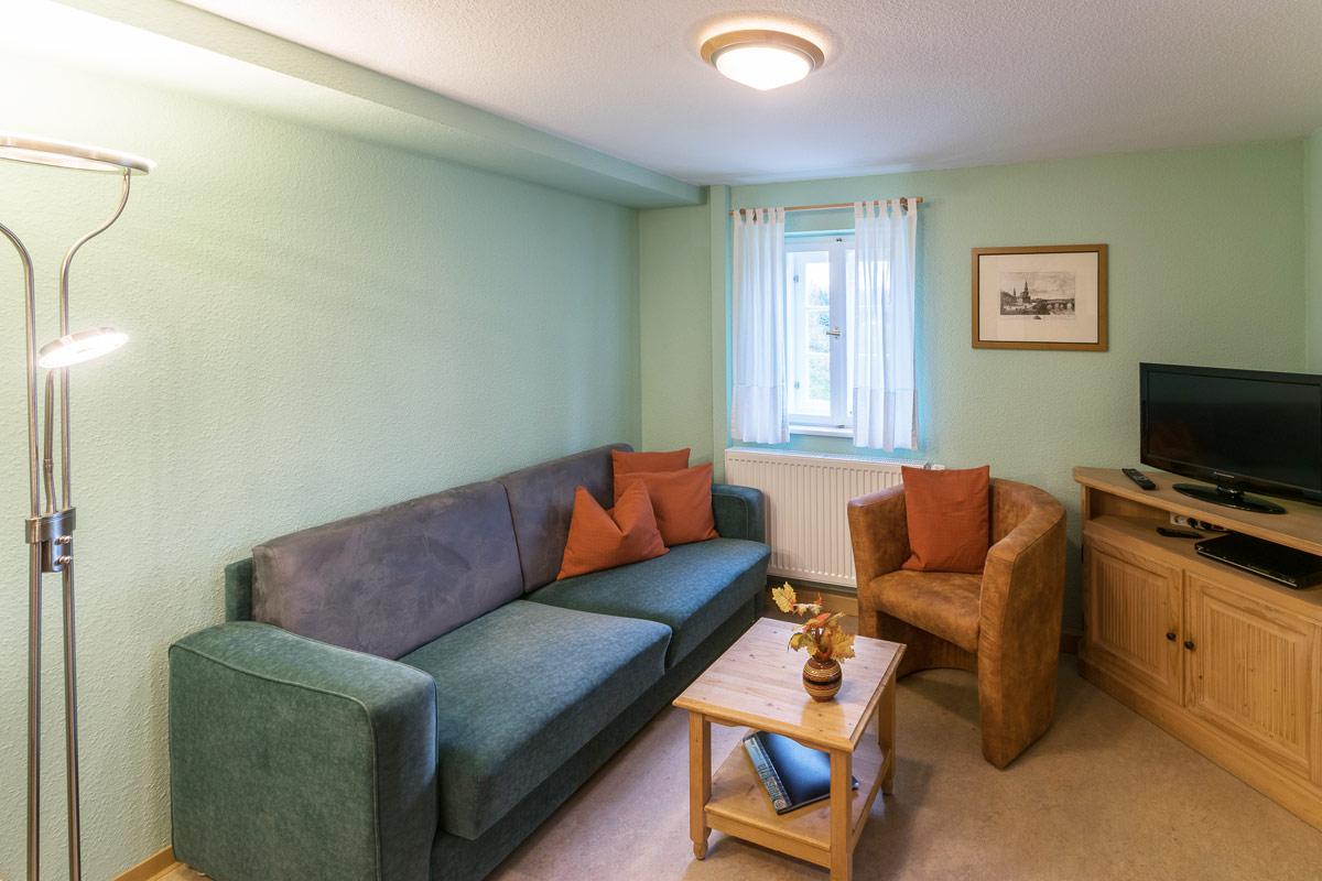 Ferienwohnung 1 im Erdgeschoss - Wohnbereich mit Couch und TV