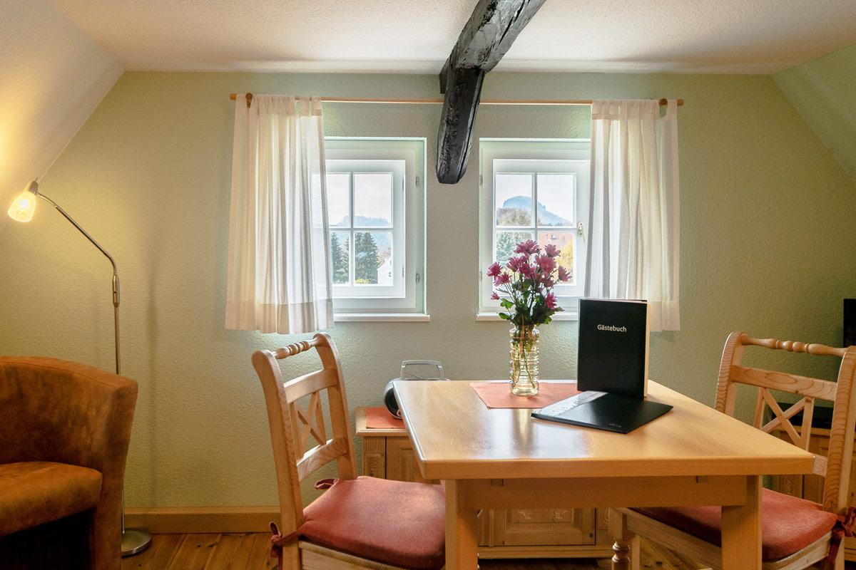 Ferienwohnung 3 im Dachgeschoss - Wohnbereich mit Esstisch und Gästebuch