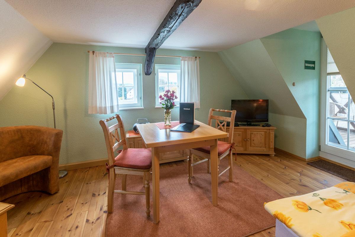 Ferienwohnung 3 im Dachgeschoss - Wohnbereich mit TV und Esstisch